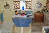 Photo shows the dining area of a 1935 Masterbilt Pioneer Trailer, with bathtub hidden one of the dining room bolsters