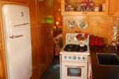 Restored fridge, gas stove and kitchen cabinets in 1938 Kozy Coach Trailer