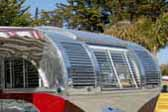 Front curved window and polished louver panels on a restored Aero Flite Travel trailer