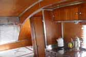 Beautiful wood paneling and cabinetry with stainless steel trim, in an Aero Flite vintage trailer
