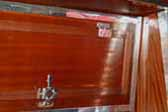 Photo of ornate polished hinges and latch on ceiling cabinetry in a vintage Aero Flite trailer