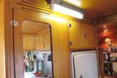 Photo shows the original ceiling light fixture in a vintage 1948 Vagabond trailer hallway