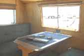 Photo shows dining table and upholstered bench seats in 1949 Curtis Wright Trailer