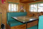 Photo of upholstered bench seats and dining table in vintage 1949 Star Trailer