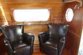 Living room with classic leather arm-chairs in 1950 Airfloat Land-Yacht vintage trailer