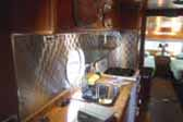 1950 Airfloat Land-Yacht travel trailer with a great retro quilted stainless steel backsplash in kitchen