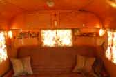 Photo shows the warmly inviting living room in a restored 1950 Vagabond trailer