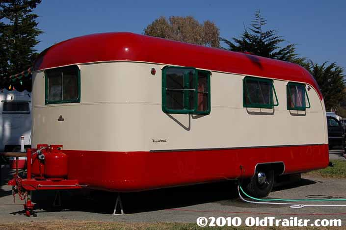 This 1950 Vagabond trailer is painted red and creme with dark green window frames