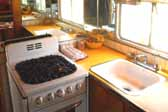 Photo shows kitchen with bright yellow plastic laminate counter in a 1950 Vagabond trailer
