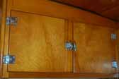 Photo shows kitchen cabinets with original hinges and latches in a 1951 Vagabond trailer