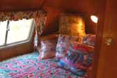 Photo of the cozy back bedroom in a restored 1951 Vagabond vintage trailer