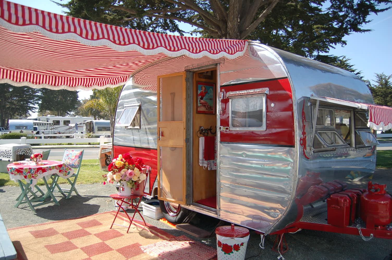 Close Up Picture Of A 1954 Dalton Vintage Trailer With Red And White Striped Awning