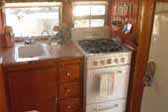 Interior shot shows kitchen in 1955 Aljoa Sportsman Trailer, with a vintage Dixie stove & oven unit