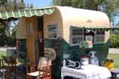 Restored vintage 1955 Aljoa Travel trailer painted green and white, with striped awnings