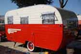 Classic 1955 Aljoa Travel Trailer riding on red rims with baby moon hubcaps and wide whitewall tires
