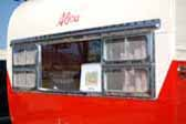 Restored and polished original front window frame on a classic 1955 Aljoa travel trailer