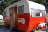 Restored 1955 Aljoa travel trailer with propane tanks painted red and white to match the trailer