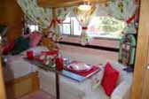 Photo shows beautifully decorated dining area in 1955 vintage Aljoa trailer