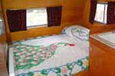 Photo of beautiful peacock bedspread in 1956 Shasta Trailer
