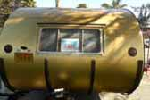 Beautiful 1957 Airfloat Cruiser trailer with stock gold aluminum siding and curved protective ribs on rear-end