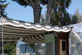 1957 El Rey trailer with muted gray and white canvas side awning