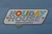 Original Holiday House logo emblem logo next to entryway door on 1960 vintage Holiday House travel trailer