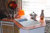 Photo of the beautifully mid-century angled kitchen counter top and cabinets in a rare 1961 vintage Holiday House trailer 24-ft.