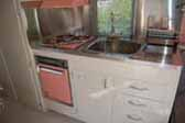 Photo of kitchen cabinets and amazing stainless steel counter top in 1961 Holiday House vintage trailer