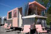 Photo of beautifully restored 1961 Holiday House travel trailer painted bright pink and white