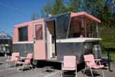 Iconic 1961 Holiday House vintage trailer with matching pink lounge chairs