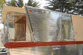 Photo shows amazing angles and polished aluminum siding on front of 1962 Holiday House Model-18 vintage trailer