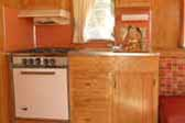 Photo of Restored kitchen woodwork and appliances in 1962 Holiday House Model-18 trailer