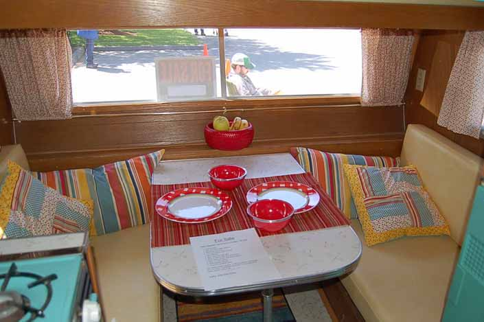 Photo shows a beautifully restored dining area in a vintage Aladdin Genie travel trailer