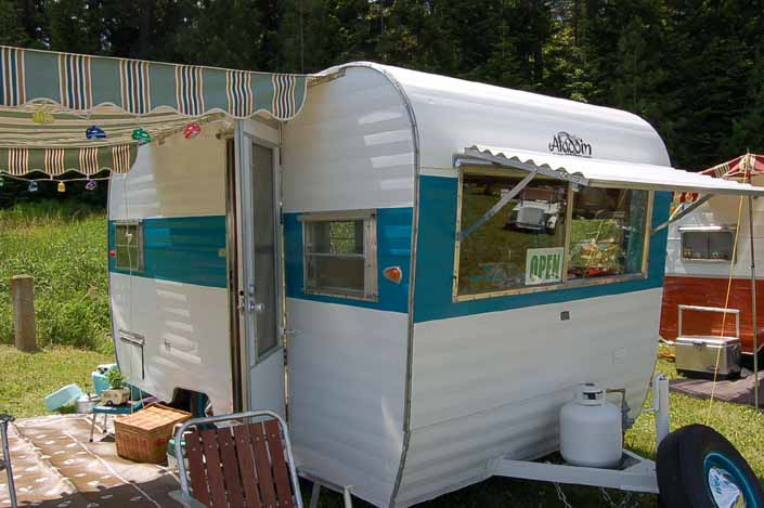 Photo of a beautiful vintage Aladdin trailer with a striped side awning and front fiberglass window shade