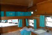 Bedroom area with plenty of storage above, in the interior a nicely restored Aladdin vintage trailer