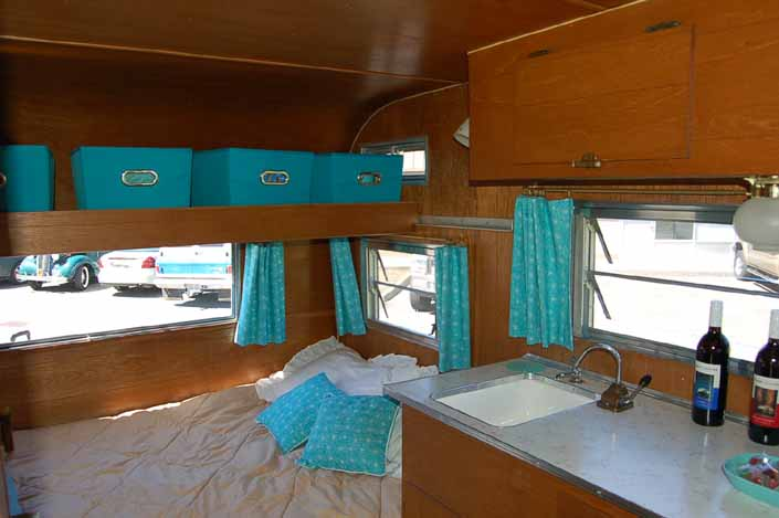 Cozy bed and beautifully re-finished woodwork with overhead storage bins in an Aladdin vintage travel trailer