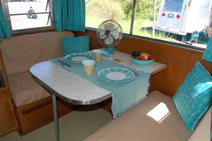 Images shows the beautifully restored dining area in an Aladdin vintage travel trailer