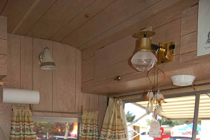 Photo of the original propane light fixture over the dining table in an Aladdin Magic Carpet Model Trailer