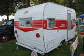 Photo shows the rear end of a red and white Magic Carpet vintage trailer built by the Aladdin Trailer Company