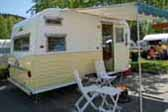 Beautifully restored 1966 Aloha travel trailer painted in buttercup yellow and white colors