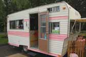 Great pink and white retro paint job on the exterior of a vintage Aladdin trailer