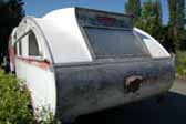 Rear-end view of an original Aero Flite vintage trailer - rough but perfect for restoration
