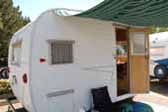Clean vintage Aloha travel trailer with striped canvas side awning