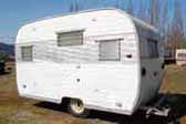 Photo of unrestored vintage Aloha trailer with original quilted aluminum side panel