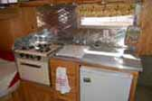 Beautiful kitchen countertop, stove and cabinets in vintage Aloha travel trailer