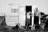 Government photo shows a young family with their 1940's vintage canned ham travel trailer, at the Hanford Trailer Camp in Washington