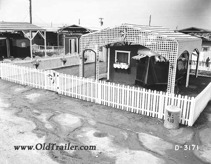 Government photo shows a 1940's vintage travel trailer under a white lattice sun cover at the Hanford Trailer City