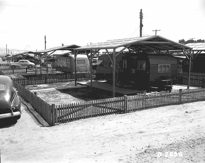 Government photo shows a wooden shade cover built over a beautiful 1940's vintage trailer, at the Hanford Trailer Camp in Washington