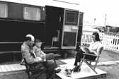 Vintage photo shows a family and their dog, sitting outside their 1940's vintage trailer, at the Hanford Trailer Camp in Washington