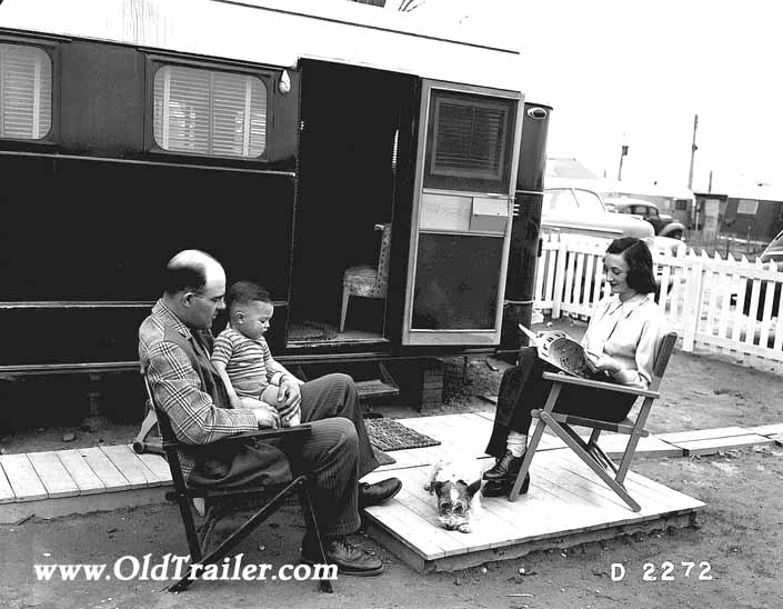 Government photo shows a family and their dog, sitting outside their 1940's vintage trailer, at the Hanford Trailer Camp in Washington